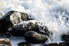 在波浪下的一些黑石头 免版税图库摄影