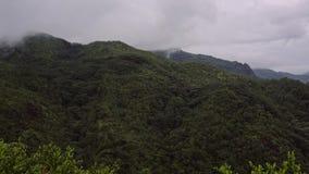 在海岛上的绿色山多云多雨天气的,山的上面掩藏在白色云彩下 影视素材