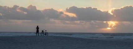 在海滩的人观看的日落与自行车 免版税图库摄影