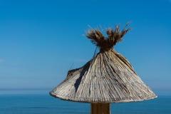 在海滩的美丽的木伞 免版税库存照片