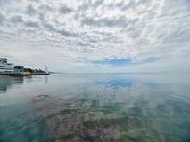 在海的低密集的云彩 与Pebble海滩和旅馆的海滨 免版税库存照片