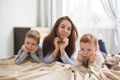 在浅兰的睡衣打扮的愉快的年轻母亲放置与她的握他们的手的两个小儿子在他们的下巴下  图库摄影