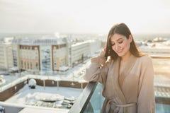 在浴巾的妇女身分在大阳台室外与城市scape 图库摄影