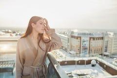 在浴巾的妇女身分在大阳台室外与城市scape 库存照片