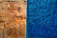 在游泳场的蓝色被剥去的水与路面边缘的热带手段的  一部分的游泳场底下背景 库存照片