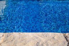 在游泳场的蓝色被剥去的水与路面边缘的热带手段的  一部分的游泳场底下背景 库存图片