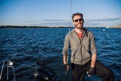 在游艇的确信和愉快的水手立场 他查找 人拿着绳索 他准备好旅行 太阳落下 免版税库存照片