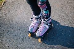 在溜冰鞋的两少女身分与在膝盖的保护在公园和举行手上 免版税图库摄影