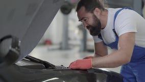 在服务站的专业汽车维护 汽车服务、修理、维护和人概念-技工人 股票视频