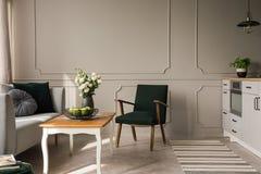 在木咖啡桌旁边的减速火箭的深绿扶手椅子用苹果和玫瑰在花瓶在厨房和客厅内部,真正 免版税库存图片