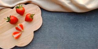 在木板材和黑暗的背景的草莓 免版税库存图片