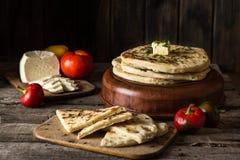 在木板的皮塔饼面包用希腊白软干酪和蕃茄和胡椒 食物静物画  英王乔治一世至三世时期烹调 西班牙食物 国家 免版税库存图片