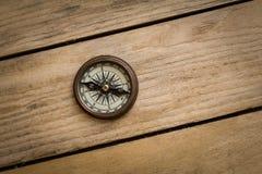 在木桌上的老指南针 免版税图库摄影
