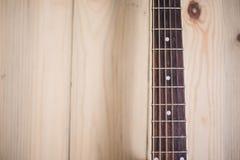 在木背景的声学吉他脖子与串 免版税库存照片