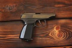 在木背景的枪 免版税图库摄影