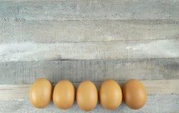 在木背景的5个布朗鸡鸡蛋 免版税库存图片