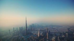 在未来派塔迪拜街市摩天大楼的美好的空中寄生虫飞行有雾的早晨日出的 股票录像