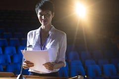 在指挥台的女实业家身分在阶段在观众席 免版税库存图片