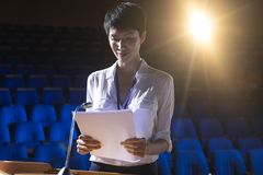 在指挥台的女实业家身分在阶段在观众席 库存照片