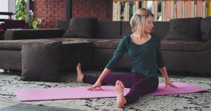 在有舒适的运动服实践的瑜伽锻炼的一个现代顶楼可爱的白肤金发的夫人舒展的身体 股票录像