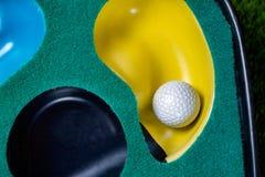 在投入席子的高尔夫球 免版税库存照片