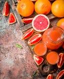 在投手的葡萄柚汁液和片断在一个切板的 免版税图库摄影