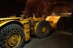 在推挤石渣外部的隧道的推土机工作 免版税库存照片