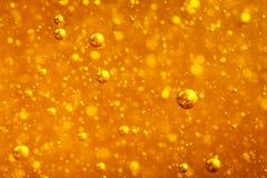 在明亮的琥珀色的颜色的抽象宏观蜂蜜泡影特写镜头 蜂蜜的纹理 健康概念的食物 饮食 免版税库存图片