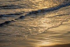 在日落的海波浪在海滩 免版税图库摄影