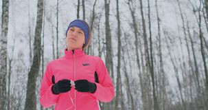在早晨冬天凹凸部前的女孩在耳朵插入耳机和准备通过自然公园跑 股票录像