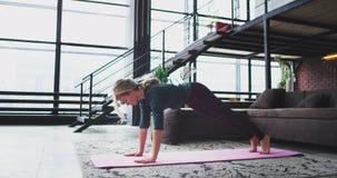 在早晨运动的少女实践的瑜伽的瑜伽锻炼舒展的身体得到整天的更多能量在 股票录像