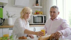 在早餐期间的美国丈夫和妻子谈话在书桌在点燃屋子里 影视素材