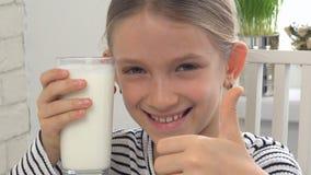 在早餐的儿童饮用奶在厨房,女孩品尝乳制品里 影视素材