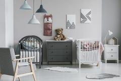 在时髦婴孩卧室墙壁上的桃红色组织者有两个小儿床和五斗橱的 库存图片