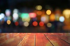 在摘要被弄脏的背景前面的空的木桌 免版税库存图片