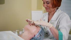 在整容术诊所的按摩治疗 医生分布在客户面孔的奶油 股票视频