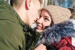 在拥抱在公园的爱的美好的年轻夫妇在一个清楚的晴朗的冬日,关闭  在彼此的男孩和女孩微笑 库存照片
