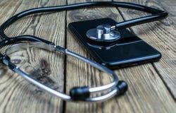 在智能手机的听诊器 智能手机修理和服务概念 概念设备健康  库存照片