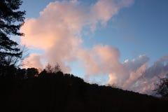 在晚上到达 日落上色清楚的天空蔚蓝和桃红色和三文鱼云彩 小山变得黑暗和黑 免版税库存照片