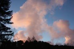 在晚上到达 日落上色清楚的天空蔚蓝和桃红色和三文鱼云彩 小山变得黑暗和黑 库存图片