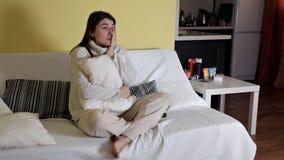 在晚上,一个极悲痛的女孩坐长沙发,哭泣,使用布料和观看的戏曲在电视 股票录像