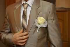 在新郎的婚姻的衣服的钮扣眼上插的花 图库摄影