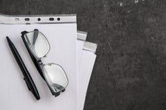 在文件的为黑装边的光学玻璃在灰色大理石背景 免版税图库摄影