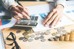 在灰色衬衣手藏品、演算与计算器和财务数据的商人分析和计数在的计算器的 免版税库存图片
