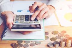 在灰色衬衣手藏品、演算与计算器和财务数据的商人分析和计数在计算器的 免版税库存图片
