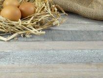 在秸杆巢的鸡鸡蛋与在木背景的粗麻布 免版税库存图片