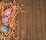 在秸杆床上的三个色的复活节彩蛋  免版税库存照片