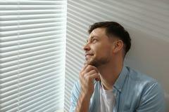 在窗口附近的帅哥与软百叶帘 库存照片