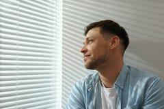在窗口附近的帅哥与软百叶帘 免版税图库摄影
