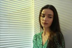 在窗口附近的年轻女人与软百叶帘 免版税库存照片